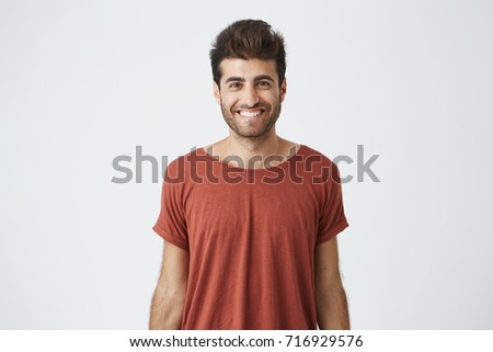 Young cheerful hispanic guy in red t-shirt brightly smiling hearing good news from friend. Beardy handsome student looking at camera with joyful smile #716929576