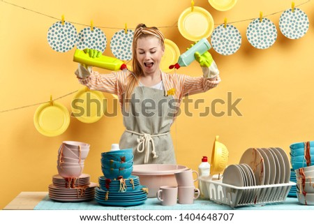 Young cheerful housewife holding two bottles with cleaner liquid for washing dishes and posing to the camera. lifestyle, spare time, free time
