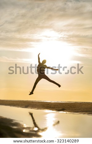 Young cheerful jumping girl silhouette in rays of sunlight at sunset on the beach. Vibrant outdoors vertical image. #323140289