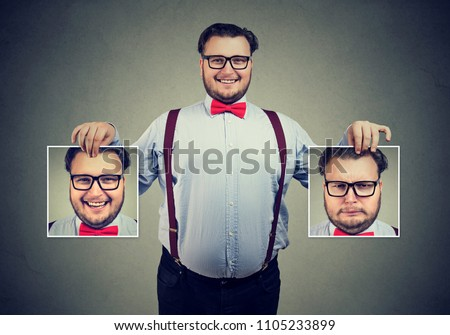 Young cheerful man in glasses holding pictures with good and bad emotions having mood swings and smiling at camera