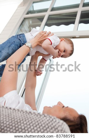 Young cheerful mother playing with cute child - stock photo