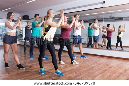 Shutterstock Young cheerful people dancing zumba elements in dancing class