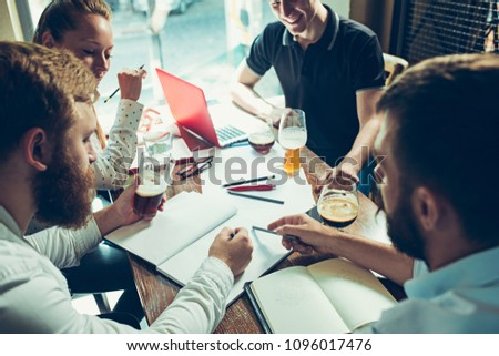 Young cheerful people smile and gesture while relaxing in pub. Team job. Photo young and mature businessmans working with new startup project. Teamwork, business, creative meeting, cooperation concept #1096017476