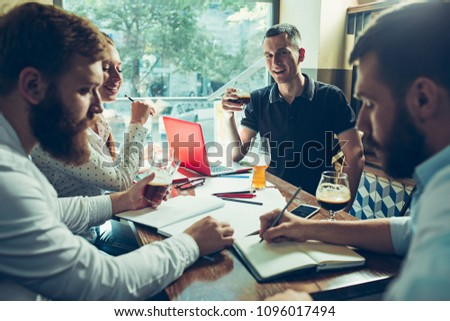 Young cheerful people smile and gesture while relaxing in pub. Team job. Photo young and mature businessmans working with new startup project. Teamwork, business, creative meeting, cooperation concept #1096017494