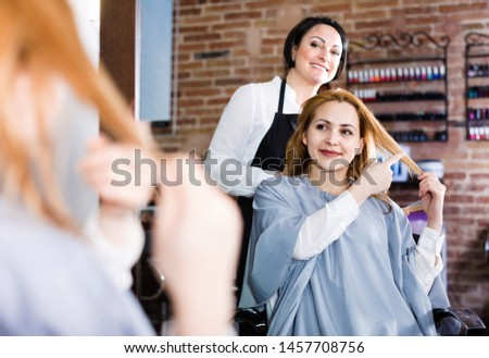 Young  cheerful positive woman points to master in hairdress salon right hair length for haircut