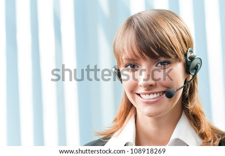 Young cheerful smiling support phone female operator in headset at office, with copyspace