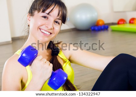 Young cheerful smiling woman exercising with dumbbells