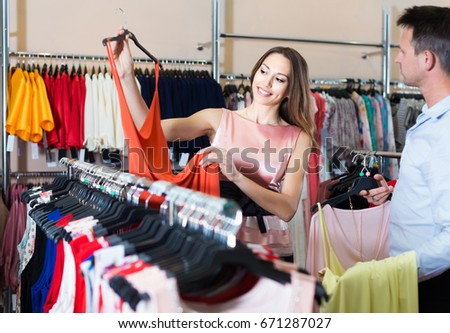Young cheerful spanish woman and man looking for new dress in showroom
