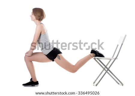 Young cheerful sporty attractive woman doing fitness training, exercises for hips and buttocks with office chair, full length isolated studio image on white background