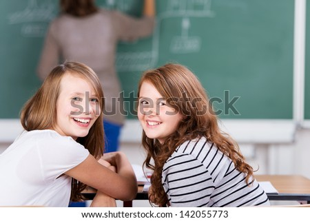 Young cheerful students during the class in schoolroom