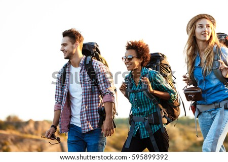 Shutterstock Young cheerful travelers with backpacks smiling, walking in canyon.