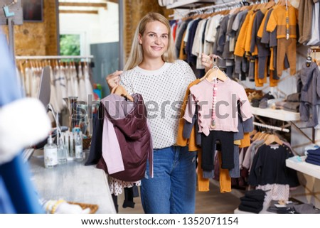 f7f0ccee9c Young cheerful woman carrying baby clothes on hangers in kids clothing  boutique  1352071154