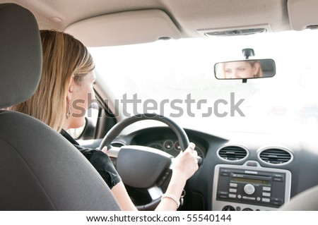 Young cheerful woman driving car - rear view, reflexion of eyes in mirror
