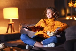 young  cheerful woman eating popcorn and watches  movie on  cable TV while switching channels with the remote control at home in evening  alone