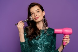 young cheerful woman holding hair dryer and cosmetic brush near face isolated on purple