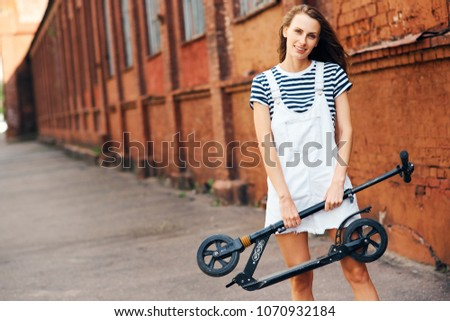 Young cheerful woman holding scooter in the summer on the street in the city. The concept of a healthy lifestyle and sport
