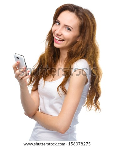 Young cheerful woman is pleased by incoming message on her phone, isolated over white