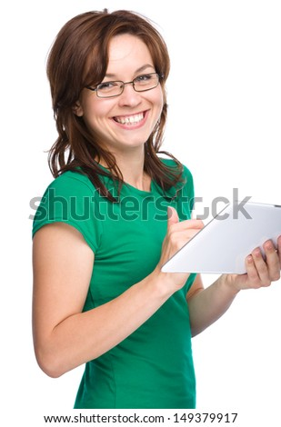 Young cheerful woman is using tablet, isolated over white