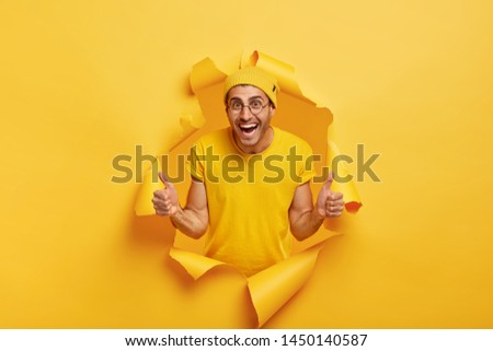 Young cheerful young male model gives thumb up gesture, stands through paper hole, smiles broadly, wears yellow hat and t shirt, demonstrates approval and agreement, agrees with awesome idea