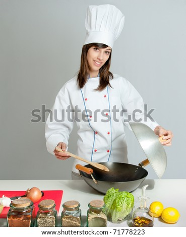 Young chef in a neutral background giving a cooking lesson