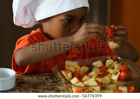 Young chef prepares carrots and parsnips for the oven.