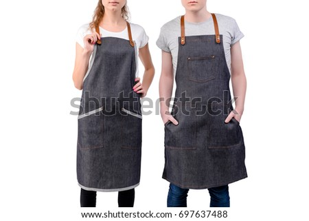 Young chefs or waiters man and woman posing, wearing aprons isolated on white background. Barista cafe coffee uniform.