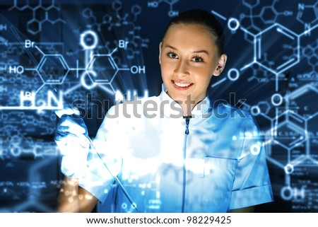 Young chemist in white uniform working in laboratory - stock photo