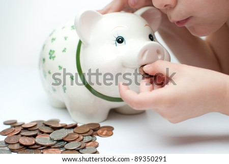 young child , boy saves change in his piggy bank