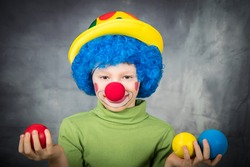 young child dressed as a clown with wig and fake nose has fun playing with colorful balls celebrating carnival