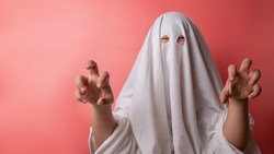 young child dressed in a ghost costume for halloween on pink background.