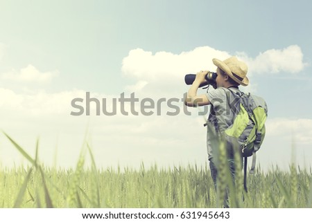 Young child explorer looks at the infinite with his binoculars