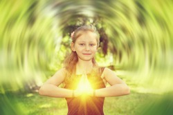 Young child girl doing yoga exercise. Concept - bright light aura in the chest area.