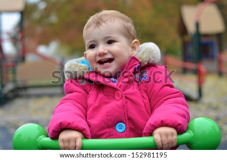 Young child, girl, having fun at the playground riding a green see-saw..