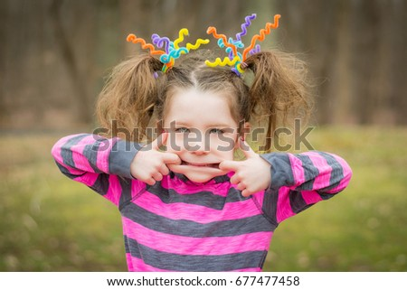 Young child girl making faces with crazy hair