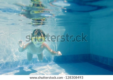 young child girl swimming underwater in pool