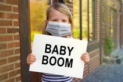 Young child girl with mask at home during the lockdown and holding a sign with the words BABY BOOM during Covid-19 Coronavirus worldwide pandemic