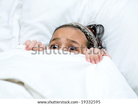 Young child hiding behind blanket while watching scary story