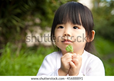 Young child holding a plant in her hand