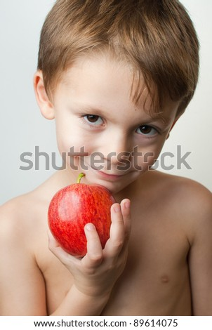 young child holding an apple on a white background - stock photo