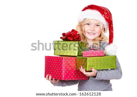 Young child holding large stack of Christmas presents wearing a Santa hat isolated on white