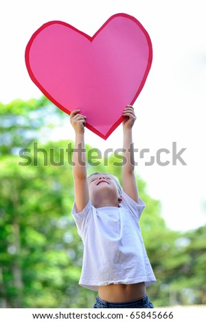 Young child holds a big pink paper heart