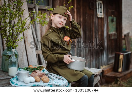 young child in military uniform on holiday day of victory, the scenery of wartime eats buckwheat porridge, field kitchen. Rustic style. Accordion, flag. May 9 2018, Russia, #1383188744