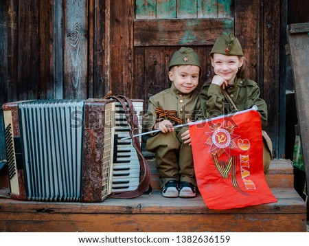 young child in military uniform on holiday day of victory, the scenery of wartime. Rustic style. Accordion, flag. May 9 2018, Russia, #1382636159