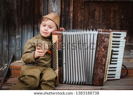young child in military uniform on holiday day of victory, the scenery of wartime. Rustic style. Accordion, flag. May 9 2018, Russia, #1383188738