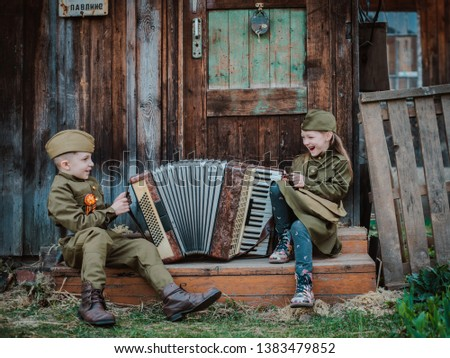 young child in military uniform on holiday day of victory, the scenery of wartime. Rustic style. Accordion, flag. May 9 2018, Russia, #1383479852