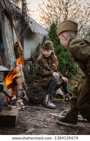 young child in military uniform on holiday day of victory, the scenery of wartime. Rustic style. Accordion, flag. May 9 2018, Russia, #1384539674