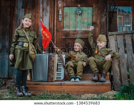 young child in military uniform on holiday day of victory, the scenery of wartime. Rustic style. Accordion, flag. May 9 2018, Russia, #1384539683