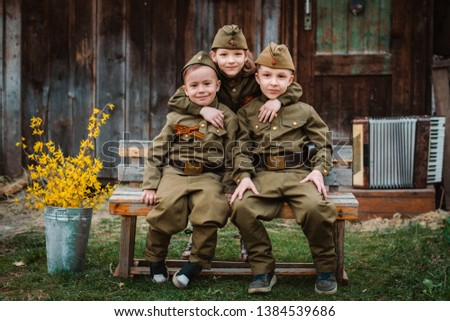 young child in military uniform on holiday day of victory, the scenery of wartime. Rustic style. Accordion, flag. May 9 2018, Russia, #1384539686