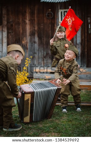 young child in military uniform on holiday day of victory, the scenery of wartime. Rustic style. Accordion, flag. May 9 2018, Russia, #1384539692