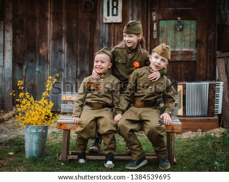 young child in military uniform on holiday day of victory, the scenery of wartime. Rustic style. Accordion, flag. May 9 2018, Russia, #1384539695
